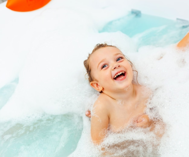 Petite fille prend un bain dans une baignoire d'hydromassage.