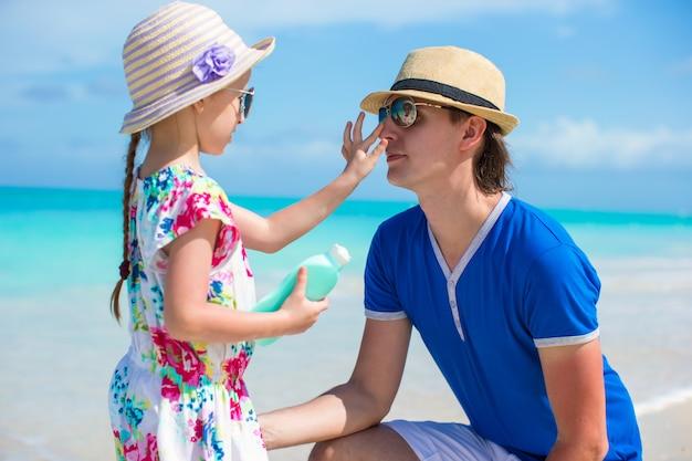 Petite fille prend de la crème solaire sur le nez de son père