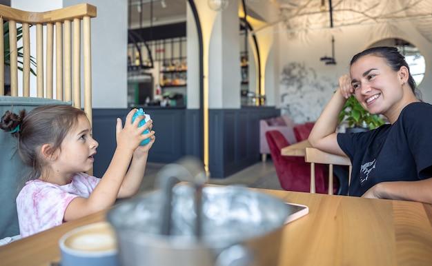 Une petite fille prend une photo de sa mère sur un appareil photo pour une impression photo instantanée.
