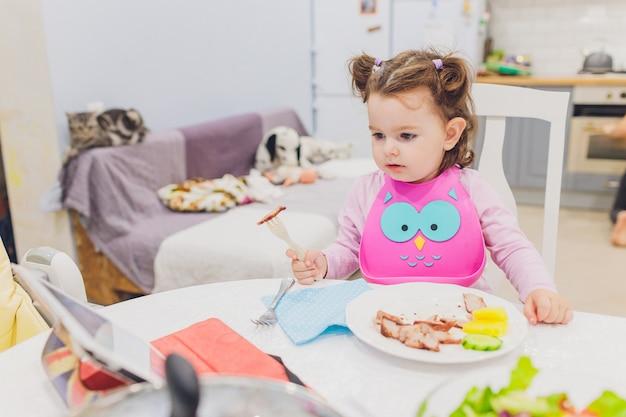 Petite fille prend son petit déjeuner en regardant le film sur la tablette.