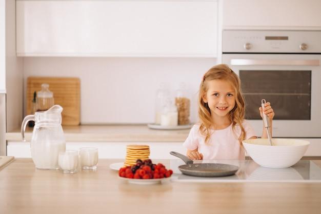 Petite fille préparant des crêpes à la cuisine