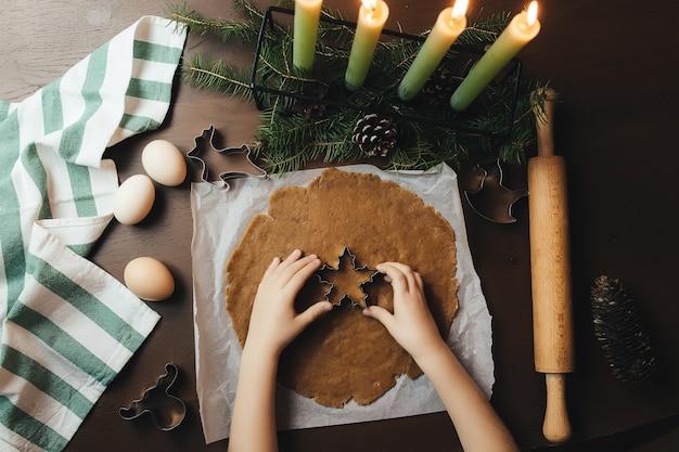 La petite fille prépare des biscuits de pain d'épice de noël. photo de haute qualité