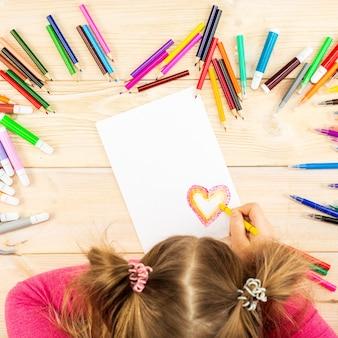 Petite fille prépare des cartes avec des coeurs pour la saint-valentin