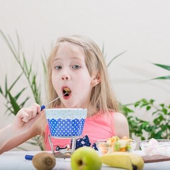 Petite fille prépare et mange une fondue au chocolat.