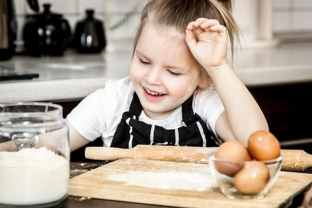 Petite fille avec préparer la tarte de vacances maison au four dans la cuisine.