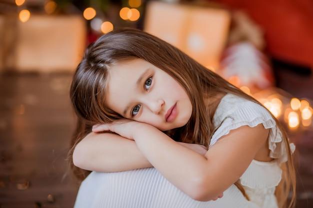 Petite fille près de l'arbre de noël souriant