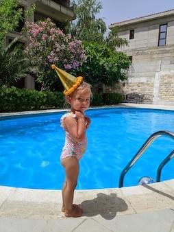 Une petite fille près de la piscine