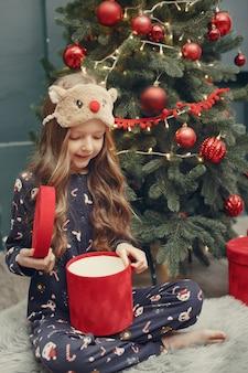 Petite fille près de sapin de noël en pyjama bleu