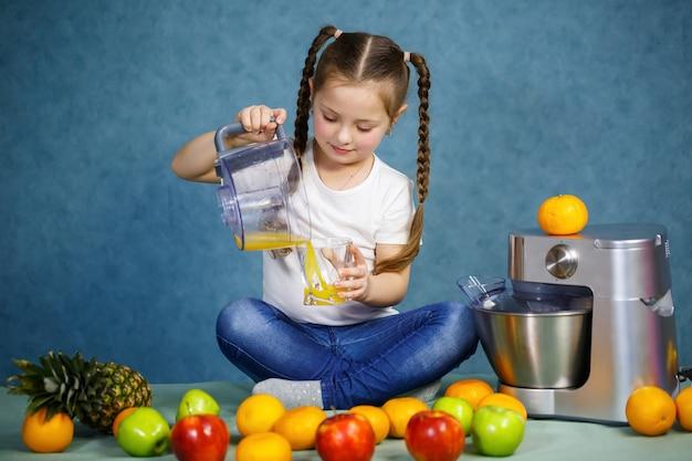 Une petite fille a pressé du jus de fruits frais de pommes et d'orange. vitamines et alimentation saine pour les enfants.