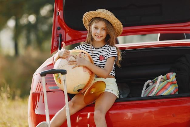 Petite fille prête à partir en vacances. kid dans une voiture rouge. fille avec globe et chapeau.