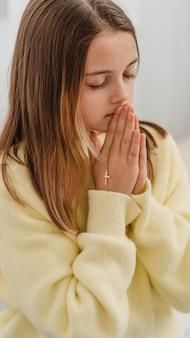 Petite fille priant avec collier croix