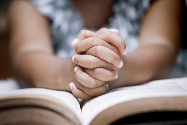 Petite fille prie avec une sainte bible