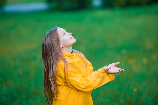 Petite fille profiter de la pluie par une chaude journée d'automne