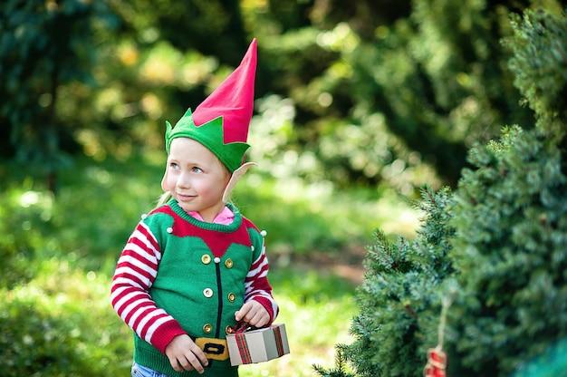 Petite fille en pull elf et chapeau attendant un noël dans le bois. portrait en demi-longueur d'un petit enfant près de l'arbre de noël