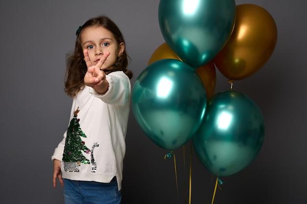 Petite fille en pull de noël se tient près de belles boules d'air métalliques vertes brillantes et dorées et montre un signe de paix, faisant des gestes avec son doigt, isolé sur fond gris avec espace de copie pour l'annonce