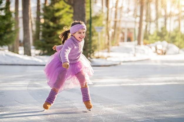 Petite fille en pull rose et jupe ample monte sur une journée d'hiver ensoleillée sur une patinoire extérieure dans le parc