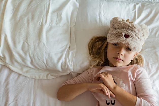 Petite fille en pyjama couché dans un lit blanc