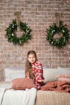 Petite fille en pyjama sur le lit dans un lit douillet pour noël