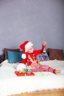 Petite fille en pyjama rouge et chapeau de père noël tient dans les mains des décorations sur l'arbre de noël.