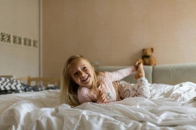 Petite fille en pyjama et les yeux bandés au lit blanc