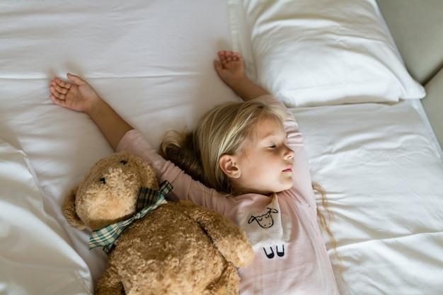 Petite fille en pyjama et les yeux bandés, couché dans un lit blanc avec ours en peluche