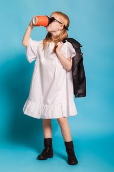 Petite fille avec des queues de vêtements et de lunettes de soleil