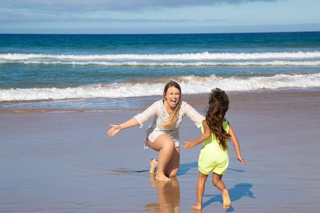 Petite fille qui court dans ses bras ouverts de maman heureuse