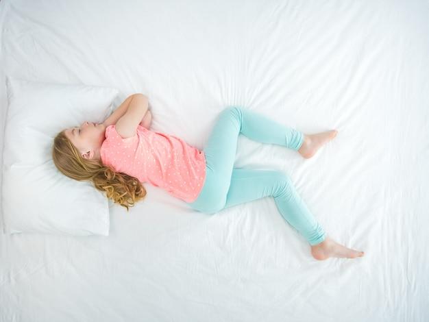 La petite fille qui dort sur le lit. vue d'en-haut. vue d'en-haut