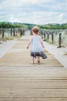 Petite fille qui longe une passerelle en bois sur la plage en été. mer méditerranée, espagne