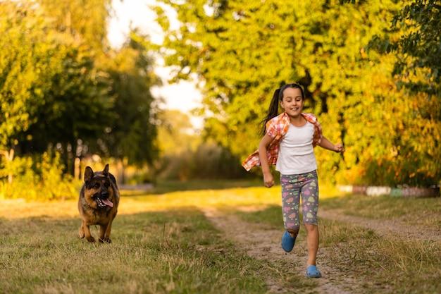 Petite fille qui marche avec un chien dans le pré