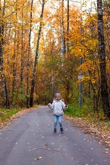 Petite fille qui marche dans la forêt d'automne en vêtements blancs en route