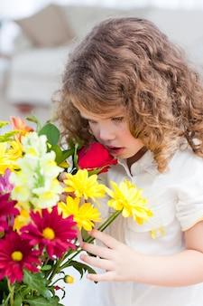 Une petite fille qui sent les fleurs
