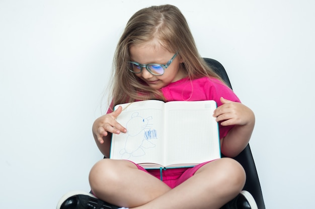 Petite fille de race blanche aux cheveux blonds et lunettes assis dans un fauteuil sur un mur de studio blanc