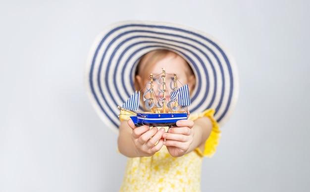 Une petite fille de race blanche dans un chapeau à larges bords tend un bateau jouet en avant.