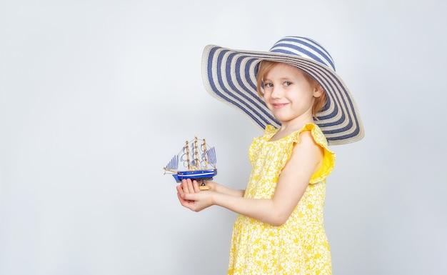 Une petite fille de race blanche dans un chapeau à larges bords tient un bateau jouet dans ses mains. le concept des vacances d'été
