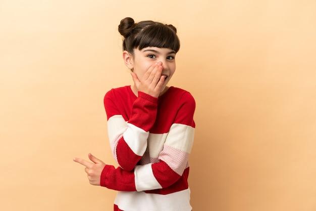 Petite fille de race blanche isolée sur un mur beige pointant vers le côté pour présenter un produit et chuchoter quelque chose