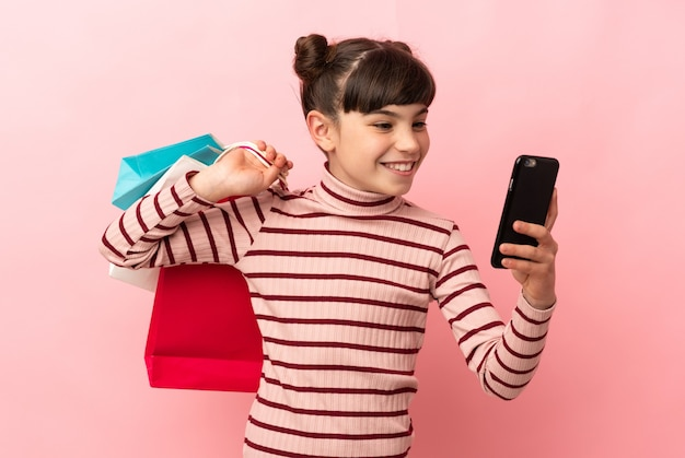 Petite Fille De Race Blanche Isolée Sur Un Mur Rose Tenant Des Sacs à Provisions Et écrire Un Message Avec Son Téléphone Portable à Un Ami Photo Premium