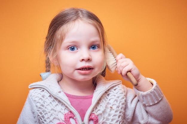 Petite fille de race blanche avec un téléphone à la main sur une couleur