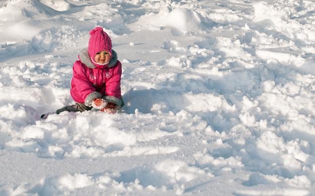 Petite fille rampant sur la neige