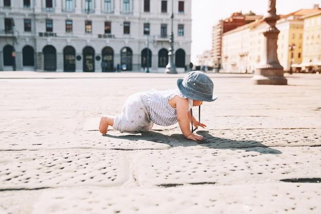 Petite fille rampant sur une rue de ville européenne à trieste italie europe enfant à l'extérieur dans une ville