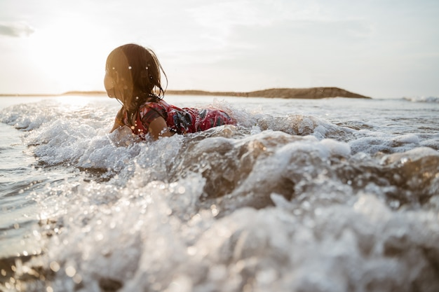 Petite fille ramper sur le sable dans la plage tout en jouant avec de l'eau