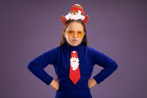 Petite fille rancunière en col roulé bleu avec cravate rouge et jante de noël drôle sur la tête regardant la caméra avec le visage fronçant avec les bras à la hanche debout sur fond violet