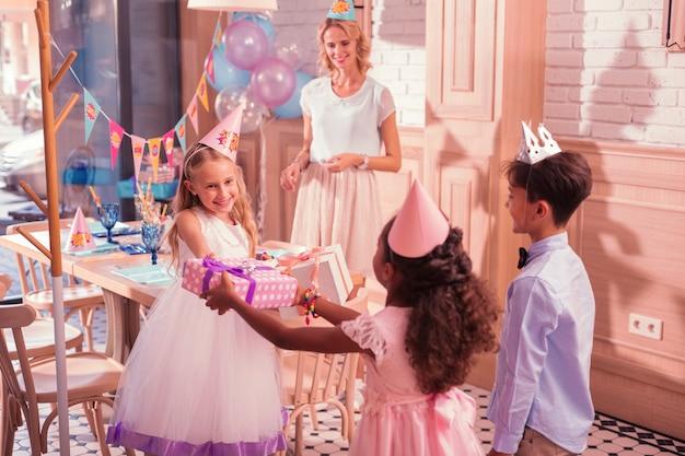 Petite fille reçoit des cadeaux d'anniversaire de ses amis