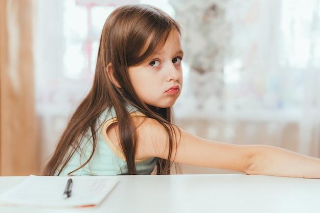 Une petite fille refuse de faire ses devoirs à la maison
