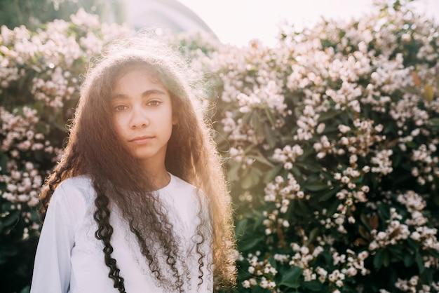 Petite fille regardant la caméra se tenant contre un champ de fleurs