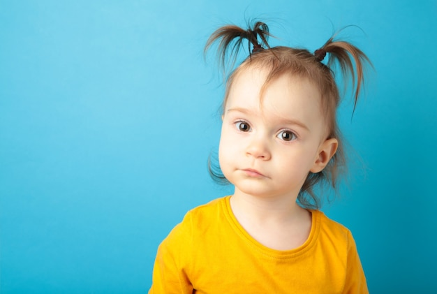 Petite fille regardant la caméra avec un sourire adorable, posant sur le bleu.