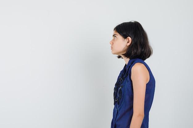 Petite fille regardant en chemisier bleu et à la recherche concentrée. .