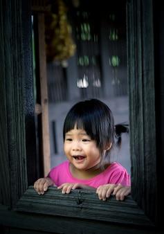 Petite fille regardant à l'extérieur de la fenêtre avec choqué et peur de quelque chose