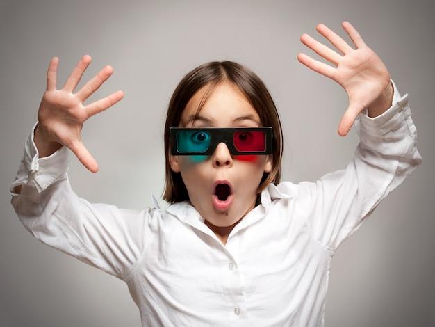 Petite fille en regardant un film portant des lunettes 3d