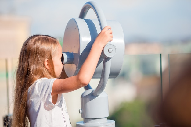 Petite fille regardant jumelles à prépaiement sur terrasse avec vue magnifique